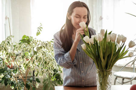 woman in blue shirt inhales, sniffs white tulips, fragrance flowers concept, flower lifestyle, enjoying aroma