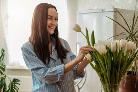 caucasian woman in blue shirt caring for white tulips in vase, nature-inspired environments, spring