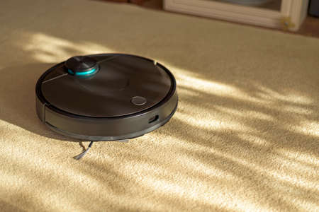 black robotic vacuum cleaner on carpet, smart appliances in the home concept