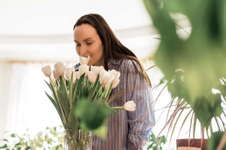 closeup woman in blue shirt inhales, sniffs white tulips, fragrance flowers concept, flower lifestyle, enjoying aroma concept, cozy home