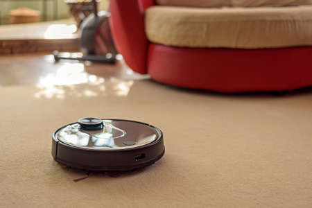Robotic floor scrubber on carpet, smart device at home concept Фото со стока