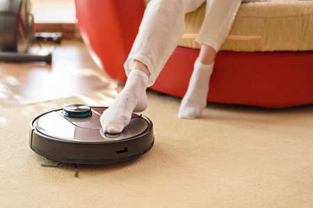 Robotic vacuum cleaner and legs on carpet, smart appliances in the home concept, lazy and comfort lifestyle concept, rest