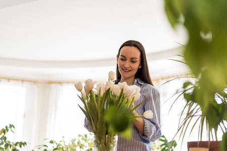 smiling happy woman in blue shirt takes care of white tulips, enjoying life, connecting with nature concept
