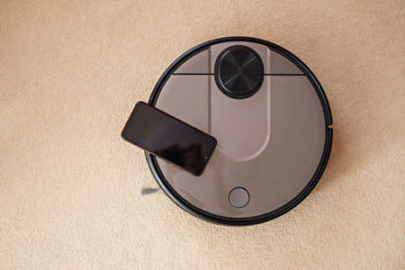 Top view Robotic floor scrubber, Robotic vacuum cleaner on carpet with smartphone, smart home Фото со стока