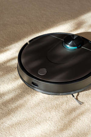 Robotic vacuum cleaner, smart appliances in the home, vertical Фото со стока