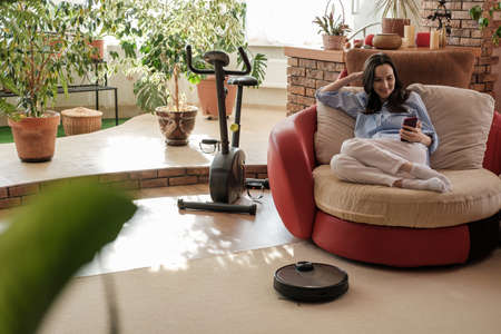 authentic woman in blue shirt with smartphone in hands at home, robot vacuum cleaner on carpet, cozy and comfortable life Фото со стока