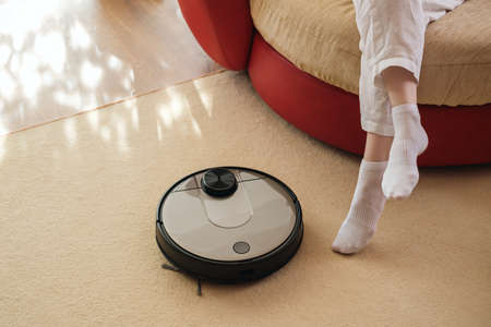 Robotic vacuum cleaner and legs on carpet, smart appliances in the home concept, lazy and comfort lifestyle concept
