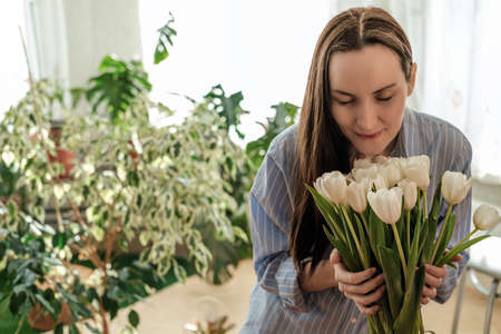 woman in blue shirt sniffs white tulips, flower greenhouse at home, flower care concept Фото со стока