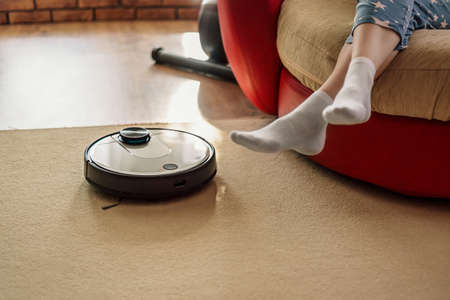 Automatic floor scrubber and legs on carpet, smart appliances in the home concept, lazy and comfort lifestyle