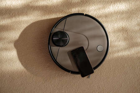 smart appliances in the home, top view Robotic vacuum cleaner with smartphone on carpet