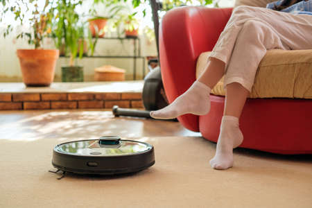 Tech house cleaning, Robotic vacuum cleaner and women legs on carpet, comfortable life, at home