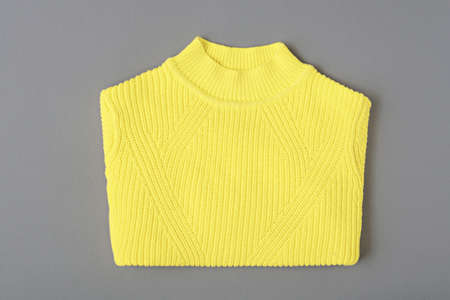 top view warm yellow sweater patterned knit on gray background, copy space