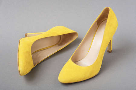 trendy color pair of yellow suede shoes on gray background