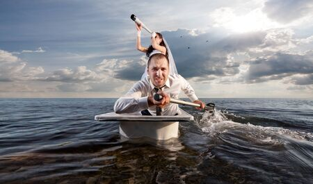 The bride and groom are sailing in the sea on a honeymoon