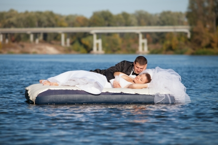 Newlyweds are floating down the river Фото со стока