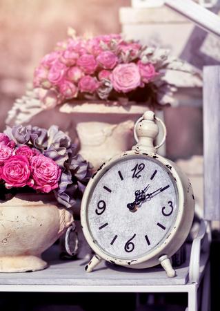 Retro alarm clock with flowers. Vintage background photo