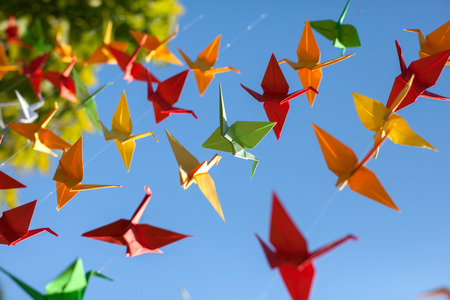 Colorful origami birds flying. Sky background.