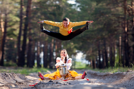 folk dancing: Beautiful womanl and man in a russian national dress outdoors