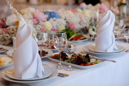 Served for a banquet table. Wine glasses with napkins, glasses and salads. Фото со стока