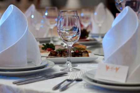 holiday catering: Wine glasses, napkins and salad on the table for the banquet Stock Photo