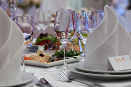 ワイングラス、ナプキン、宴会のテーブルにサラダ。