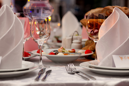 Wine glasses, napkins and salad on the table for the banquet.