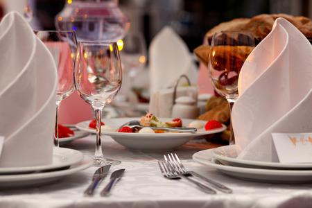servilletas: Copas de vino, servilletas y ensalada en la mesa para el banquete. Foto de archivo