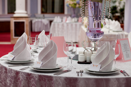 served: Served table with napkins, cards and glasses. Stock Photo
