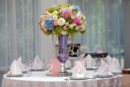 table decoration: Flowers, wine glasses, napkins and salad on the table for the banquet.