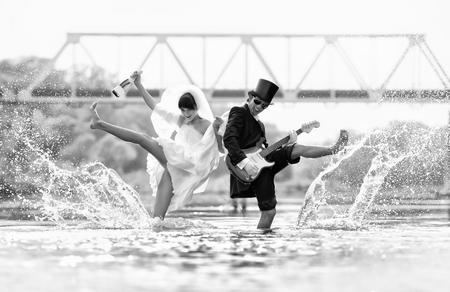 luna de miel: Novia y novio con la guitarra y el champán en el lago.