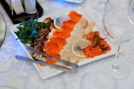 dish fish: Plato de pescado con lim�n, hojas verdes frescas Foto de archivo