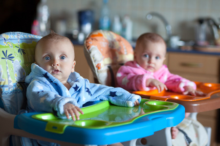 robes: Two children in robes in high chair Stock Photo