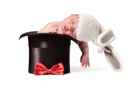 Sweet cute baby in knitted hat with a rabbit ears in the silk hat on the white background