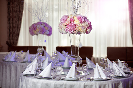 celebration event: Table setting at a luxury wedding reception. Beautiful flowers on the table.