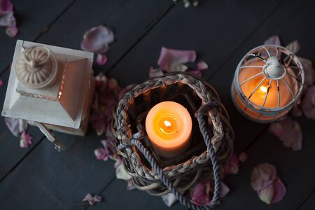 home accessories: Burning candles in a decorative basket and lantern. Petals of rose on old wooden board.