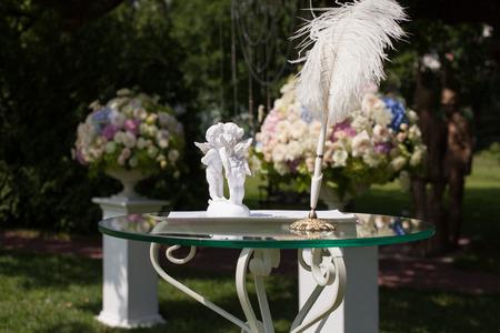piuma bianca: Amorini, penna andcertificate sul tavolo per la registrazione di nozze Archivio Fotografico