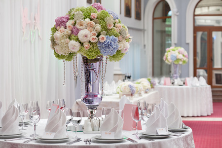 banquet table: Table setting at a luxury wedding reception. Beautiful flowers on the table.