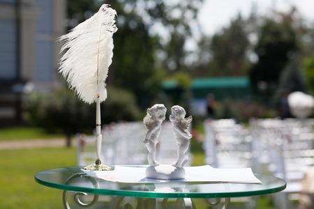 white feather: Cupidos, la pluma y el certificado en la tabla para el registro de la boda Foto de archivo