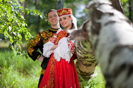 russian: A man and a woman in the Russian festive national dress on the background of the forest