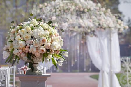 결혼식: 결혼식 아치의 배경에 꽃병에 장미의 아름 다운 꽃다발. 결혼식을위한 아름다운 설정입니다.
