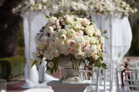 set up: Beautiful bouquet of roses in a vase on a background of a wedding arch. Beautiful set up for the wedding ceremony.