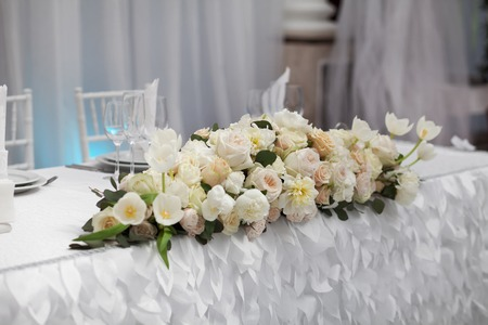 reception desk: Table setting at a luxury wedding reception. Beautiful flowers on the table.