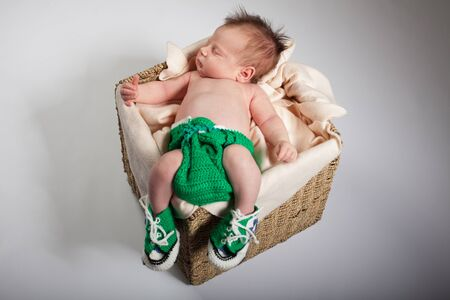 乳幼児: バスケットに彼の胃には、新生児が眠っています。スタジオで撮影します。