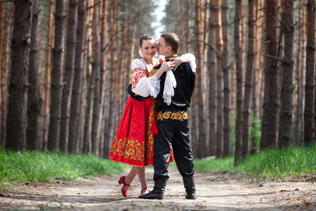 folk village: Man and woman with an accordion in the Russian national dress Stock Photo