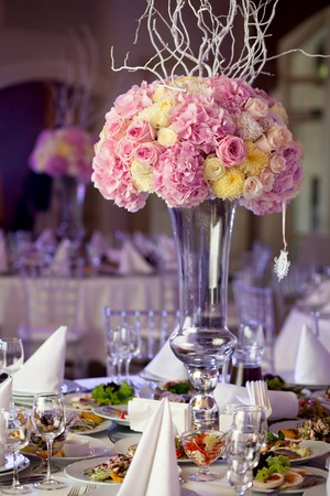 arrangements: Table setting at a luxury wedding reception. Beautiful flowers on the table.