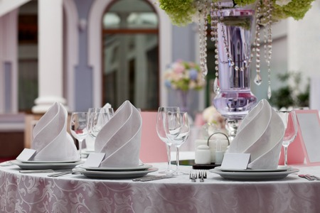 Seating card for wedding table. Wine glasses with napkins set in restaurant. Фото со стока