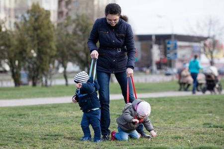 strapped: Young mother walking with her two children off the leash
