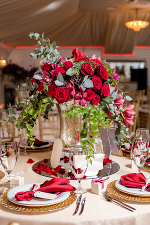 Table setting at a luxury wedding reception. Beautiful flowers on the table.