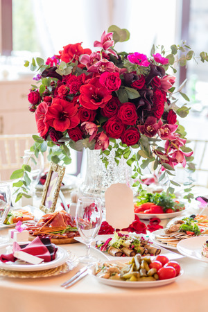 vase: Table setting at a luxury wedding reception. Beautiful flowers on the table.