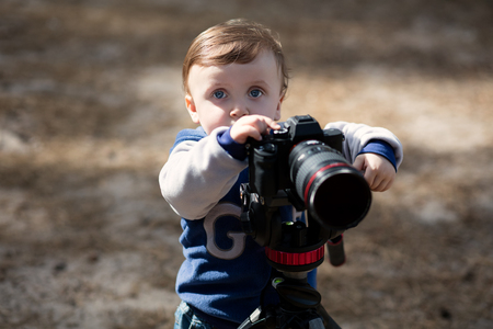Young photographer child taking photos with a camera on a tripod